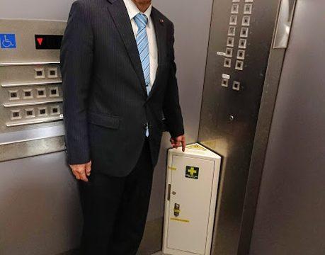 エレベーター緊急備蓄ボックスを指差す岡崎