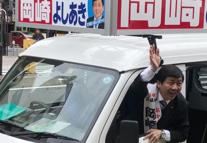 遊説カーから支持者に手を振る岡崎